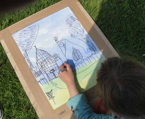 Isabel drawing the church over her watercolour background