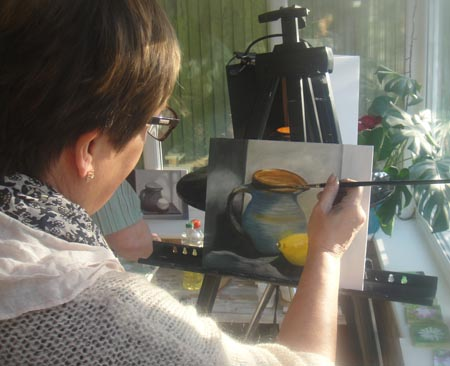 Jude puts finishing touches to her oil painting.